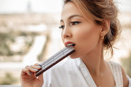 young beautiful Asian girl in beige lace shorts,white shirt eating a chocolate bar on the balcony. selective focus. small focus area.