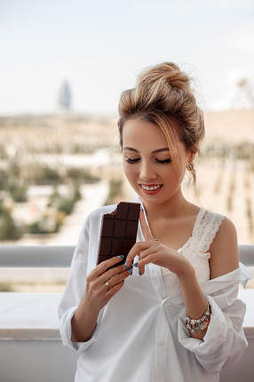 young beautiful Asian girl in beige lace shorts,white shirt eating a chocolate bar on the balcony. selective focus. small focus area