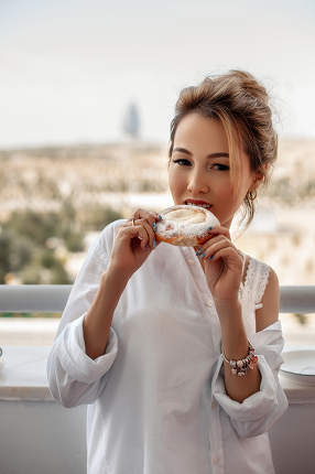 young beautiful Asian girl in beige lace shorts,white shirt eating dessert, pie on the balcony. selective focus. small focus area