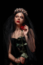 young beautiful girl in a black headband and black veil in a corset with a scarlet rose in her hands on a black isolated background