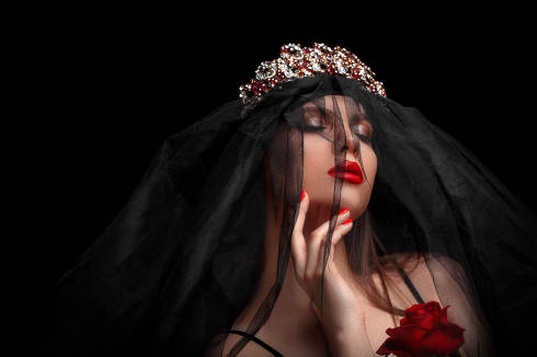 young beautiful girl in a black headband and black veil in a corset with a scarlet rose in her hands on a black isolated background.
