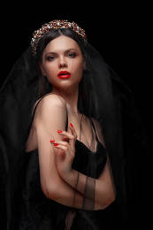 young beautiful girl in black headband and black veil on black isolated background