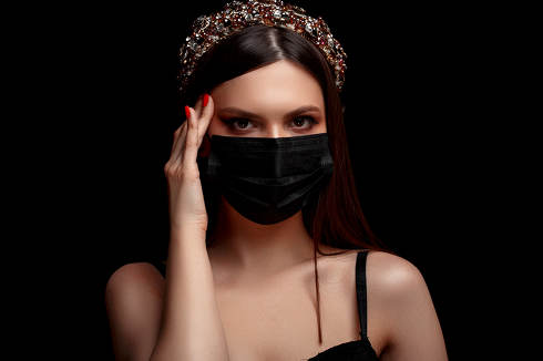 young beautiful girl with a headband on her head in a black medical mask on a black isolated background