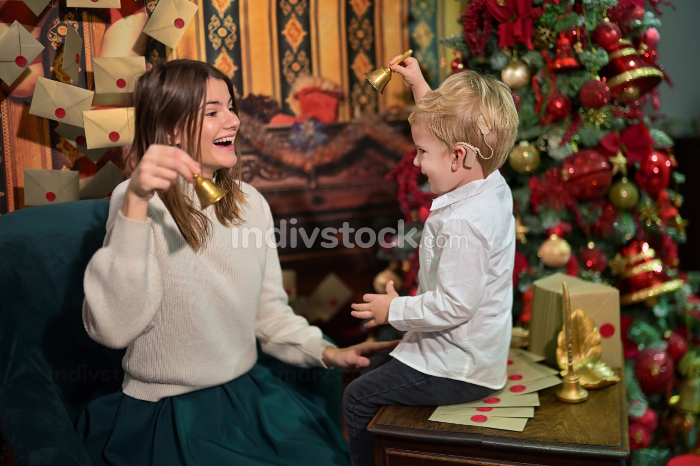 A Boy with Cochlear Implants play with Christmas Bell with his Mother