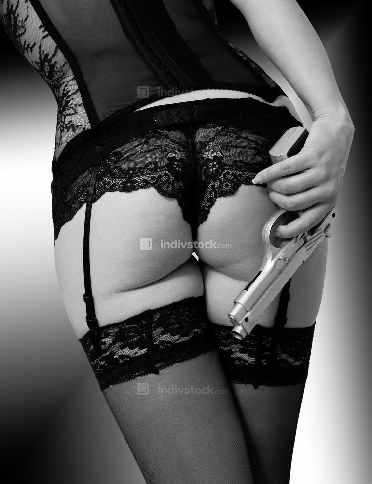 Body of a woman in black lingerie with a pistol in the hand