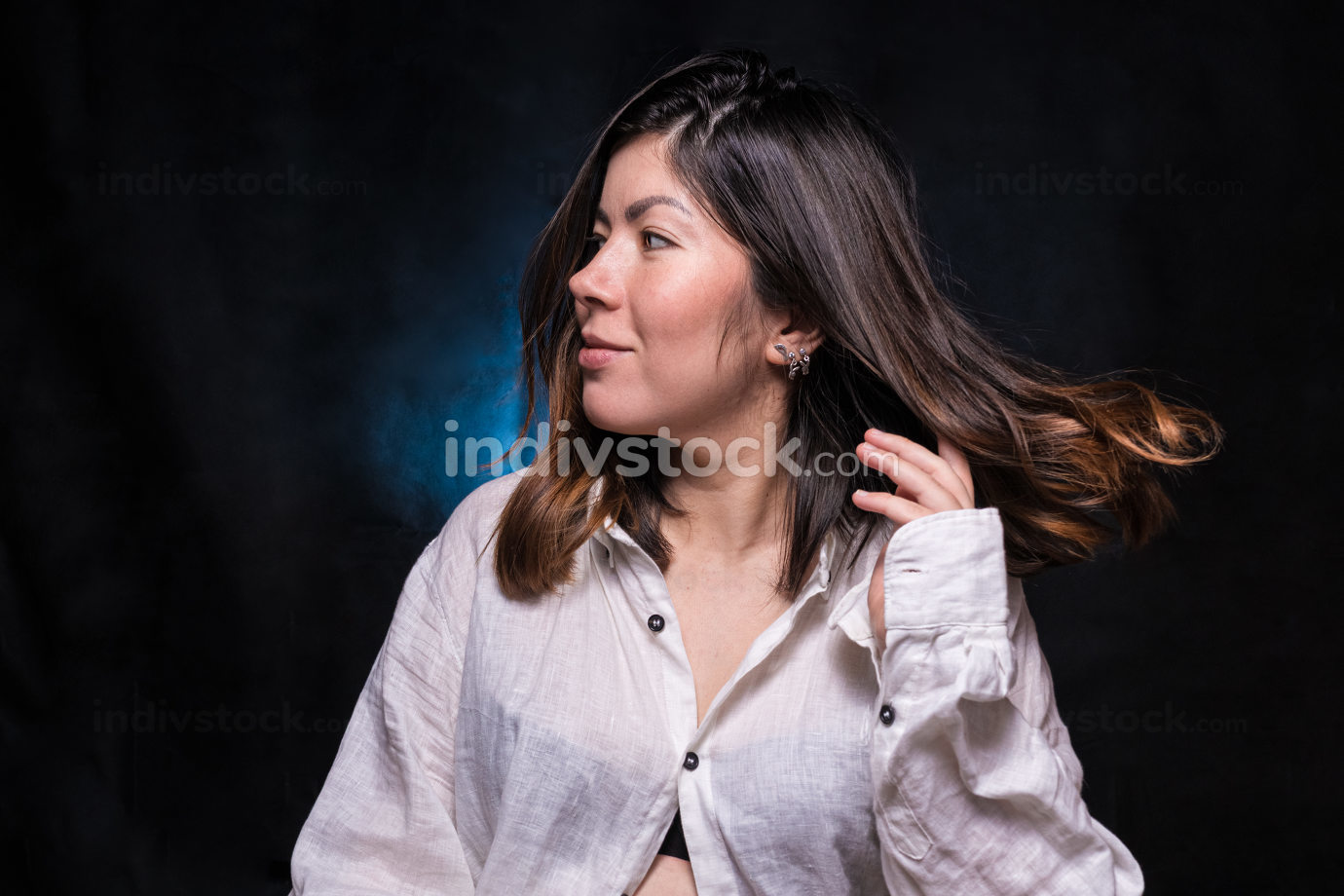 cheerful young brunette girl in a white shirt straightens her hair with her hand