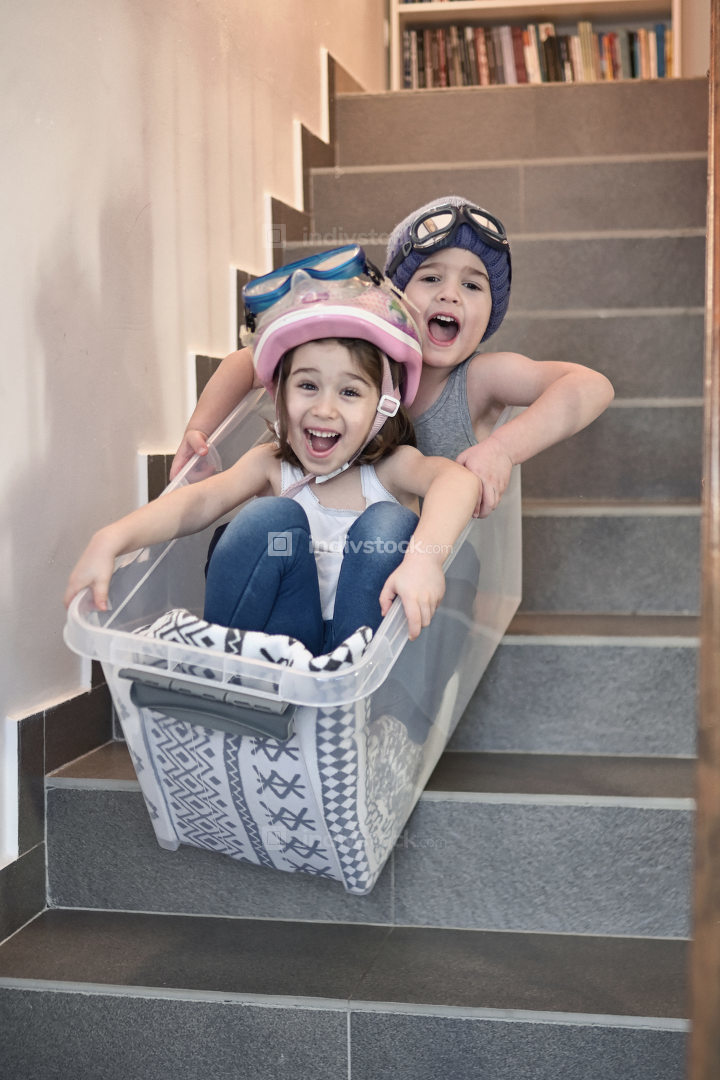 Kids sledding down stairs in a storage box. Kids having fun sledding down stairs in a storage box