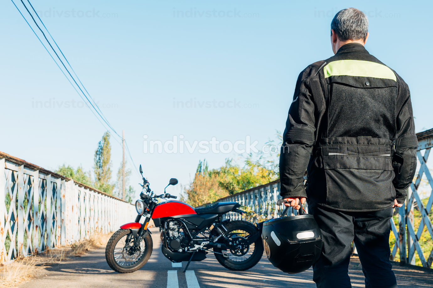 man 40s, man on his back looking at a motorcycle with a helmet in his hand.