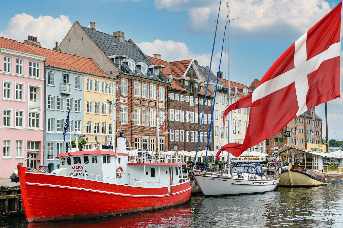 Nyhavn a 17th century harbour in Copenhagen with typical colorful houses and boats with national flag of Denmark on the first ground