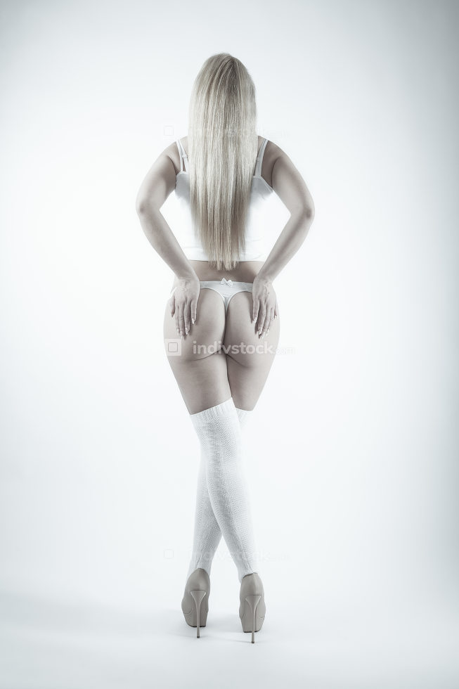 Rear view of a blonde woman in white lingerie, stockings and hig