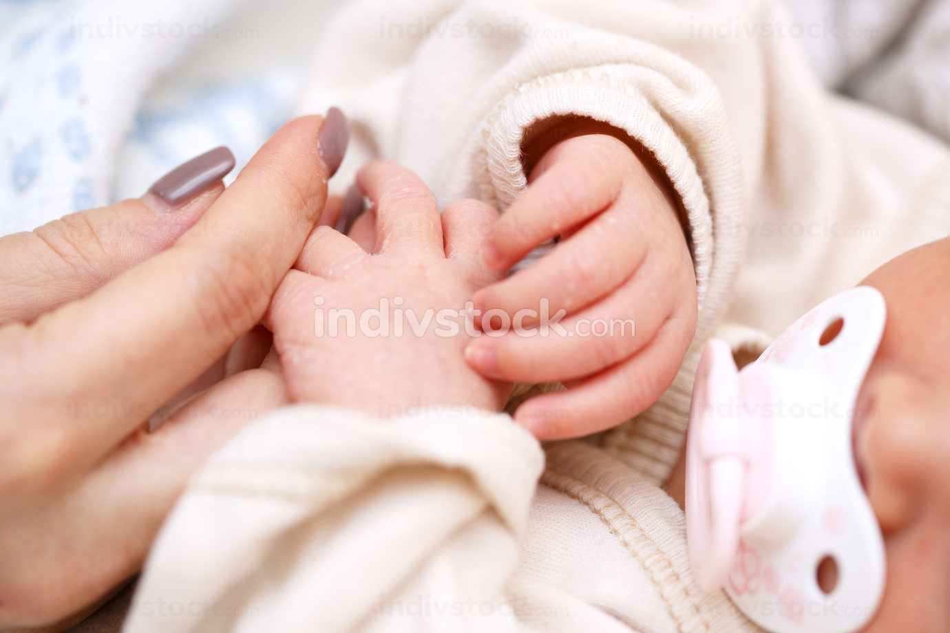 small fingers, hands of a newborn baby close-up. baby has pacifier in her mouth . small depth of focus area