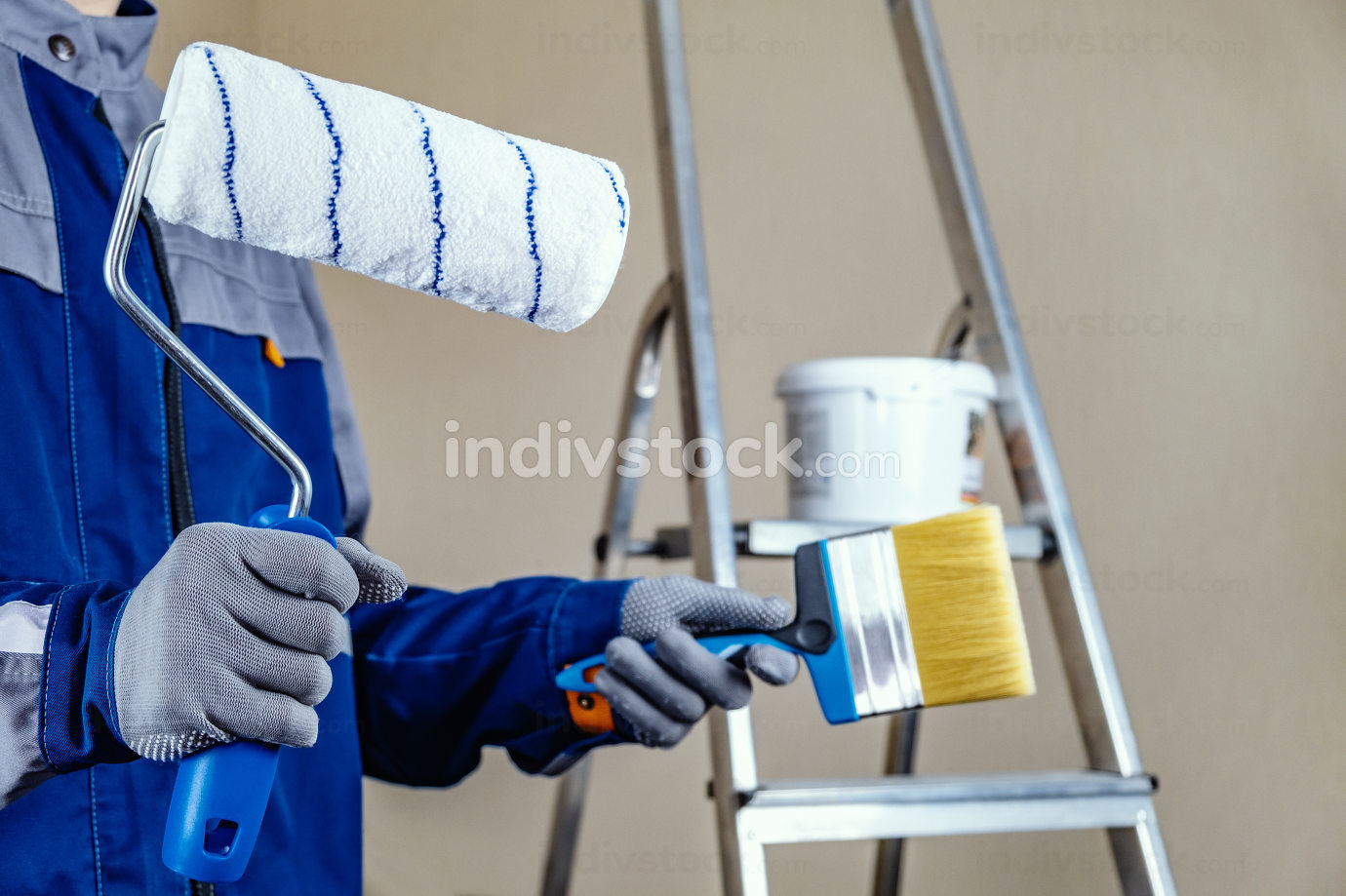 The plaster painter is ready to paint the wall. In the hands of a roller and brush. A stepladder and a bucket of paint in the background