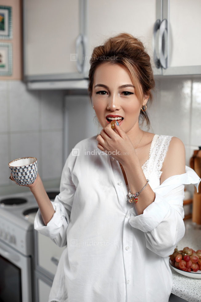 young beautiful Asian girl in beige lace shorts,white shirt drinking coffee . selective focus. small focus area