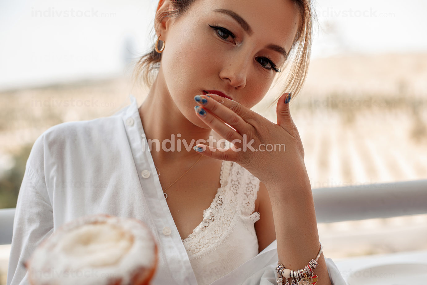 young beautiful Asian girl in beige lace shorts,white shirt eating dessert, pie on the balcony. selective focus. small focus area.
