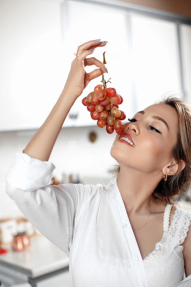 young beautiful Asian woman in beige lace shorts,white shirt eating grapes in the kitchen . selective focus: a small area of focus.