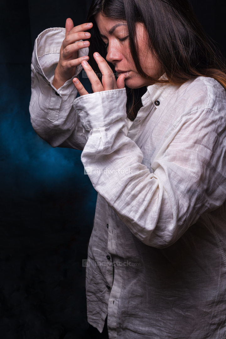 young woman with black hair who is feels bad, wearing a long white shirt, trying to cover her face with her hands