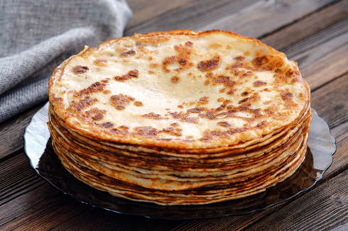 A tall stack of pancakes. Breakfast for the whole family. Maslenitsa, the holiday of the end of winter
