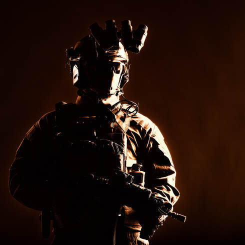Army elite forces member, modern infantryman with hidden face, in tactical ammunition, equipped radio headset, night vision device mounted on helmet, standing with short barrel service rifle in hands