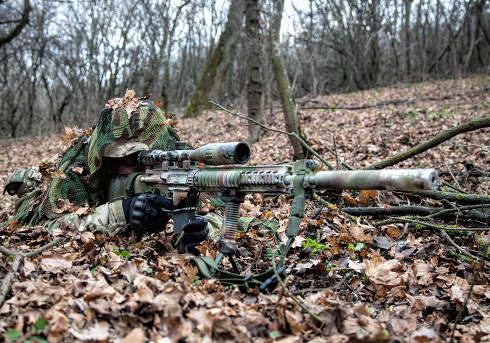 Army elite forces sniper, tactical group marksman, airsoft player lying on ground in forest, hiding in autumn foliage, covering himself with camouflage cape, searching targets through optical sight