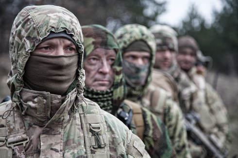 Army elite forces tactical group soldiers, skilled commandos squad, members wearing camouflage uniform, hiding faces behind masks, standing in line behind commander