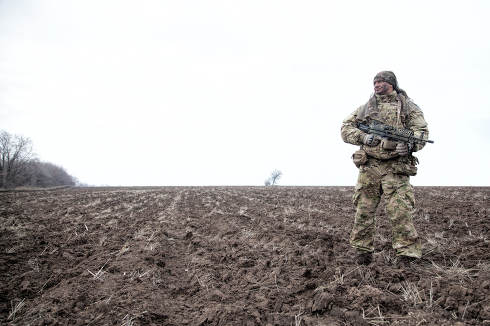 Army special forces machine gunner, elite commando in camouflage uniform, load carrier, standing on plowed field, holding medium machine gun, patrolling border line, observing area