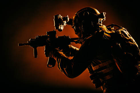 Army special operations soldier, commando fighter in full tactical ammunition, helmet with radio headset and night vision device, aiming short barrel assault rifle in darkness, low key studio shoot