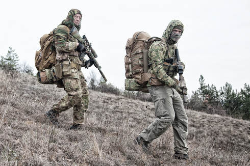 Army team members, military mercenary group in various types camouflage uniform, armed service rifles, observing territory from hill, patrolling area during mission