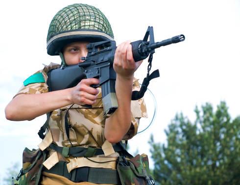 British girl soldier in desert uniform aiming her rifle