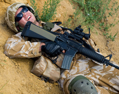 British soldier in desert uniform lying wounded