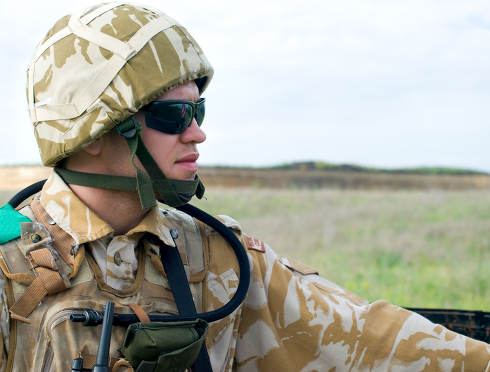 British soldier with the reflection of UK flag in glasses looking forward