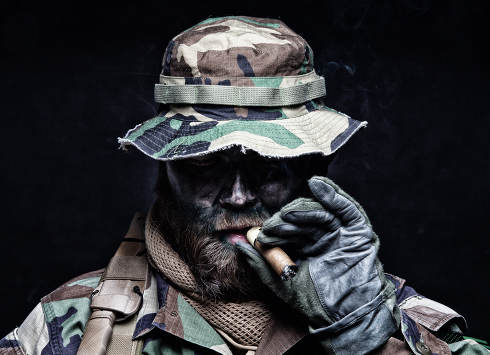Brutal and serious commando soldier, army special forces veteran, in camouflage battle uniform, boonie hat, black paint on bearded face, combat knife in shoulder holder, smoking cigar, studio portrait