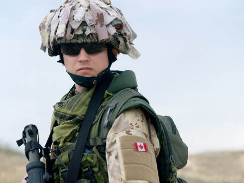canadian soldier in desert uniform holding his rifle