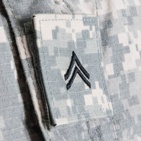Close up shoot of US army soldiers corporal rank insignia embroidered on army combat uniform collar or lapel patch on hook-and-loop fastener on pixelated grey, universal camouflage pattern fabric