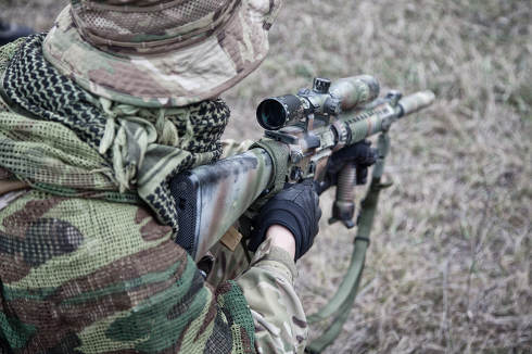 Commando marksman, army special operations sniper, rifleman sitting, standing on knee on ground, armed assault rifle with optical sight, observing area, searching targets to shoot, over shoulder view