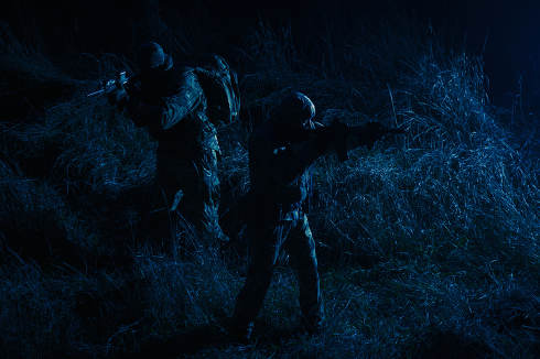 Commandos group, army special operations tactical group, military patrol team marching in field loaded with ammunition, sneaking in darkness, carefully and quiet moving in line during night mission