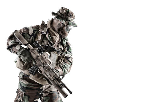 Equipped and armed with service rifle commando fighter, US army special forces soldier, marine rider in camo uniform and boonie hat, looking back, peering around corner studio shoot isolated on white
