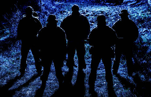 Group of armed soldiers, modern military mercenaries, secret service fighters, army special operations riflemen, commandos crew standing together in line in darkness, patrolling area at nighttime