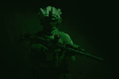 Half length, low key studio shoot of army soldier, marine infantryman in mask, camo uniform, equipped modern ammunition, armed service rifle standing in darkness with night vision device on helmet