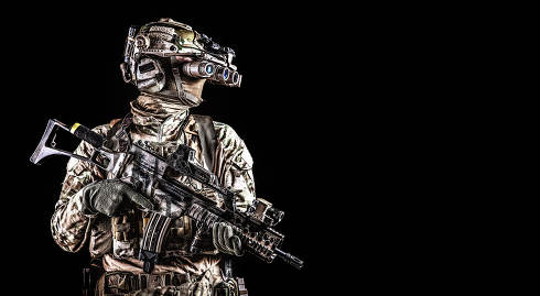 Half length portrait of army special forces rifleman, commando elite soldier equipped radio tactical headset, armed service rifle, using night vision goggles in darkness, isolated on black, copyspace