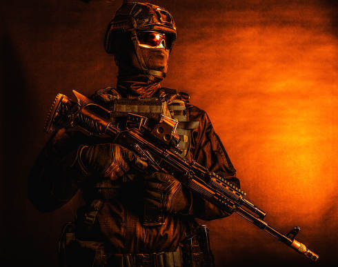 Half-length portrait of police tactical group fighter, special forces soldier, security service guard in mask and full ammunition, standing with assault rifle, low key studio shoot with red backlight