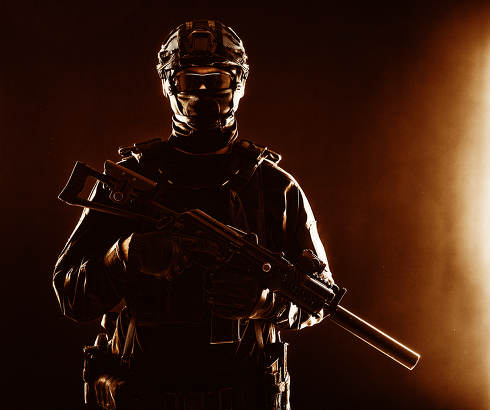Half-length portrait of special forces soldier, army commando, police tactical team or SWAT fighter with hidden behind mask and glasses face, armed assault rifle with silencer, low key studio shoot