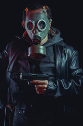 Man with gas mask and gun, dressed in black leather jacket