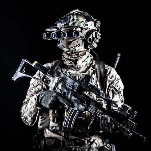 Marine rider in camouflage uniform and face mask, patrolling in darkness with quad-tube night vision goggles on battle helmet, holding modern assault rifle, low key studio portrait on black background