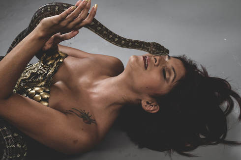 Model, Sensual tattooed woman with big snake and iron corset