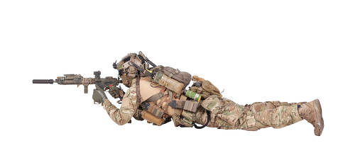 Modern army soldier, infantry rifleman equipped with tactical ammunition and radio, lying on ground, observing territory trough optical sight, aiming, shooting with assault rifle isolated studio shoot
