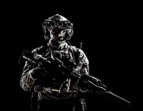 Modern army special forces equipped soldier, anti terrorist squad fighter, elite mercenary armed assault rifle, standing in darkness with night vision goggles on helmet, studio portrait, copyspace
