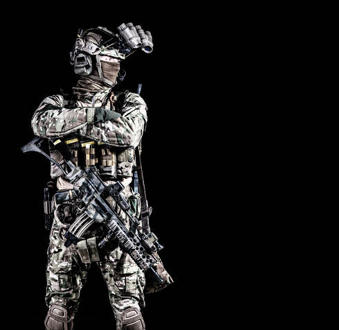 Modern combatant, army special forces soldier, counter terrorist squad mender in full ammunition, hiding face behind mask, equipped night vision device, standing with arms crossed on chest, copyspace