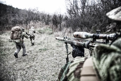 Modern warfare combatants group, commando fighters squad, team members attacking, rushing trough woodland. Sniper or marksman covering comrades in forest, over shoulder view