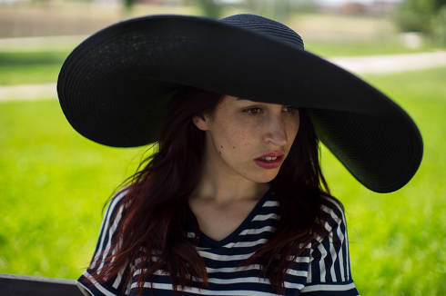 Picture hat, girl in a park in spring