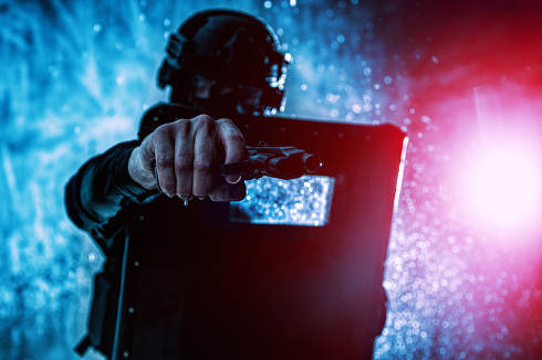 Police counter terrorist, anti narcotics, quick response tactical group fighter, SWAT team member aiming service pistol in camera, shooting with handgun while hiding behind armored ballistic shield